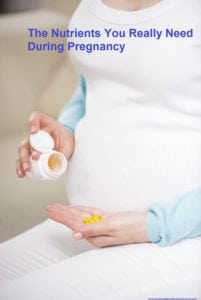 Close-up of pregnant woman sitting at sofa with vitamin pills in her hand.