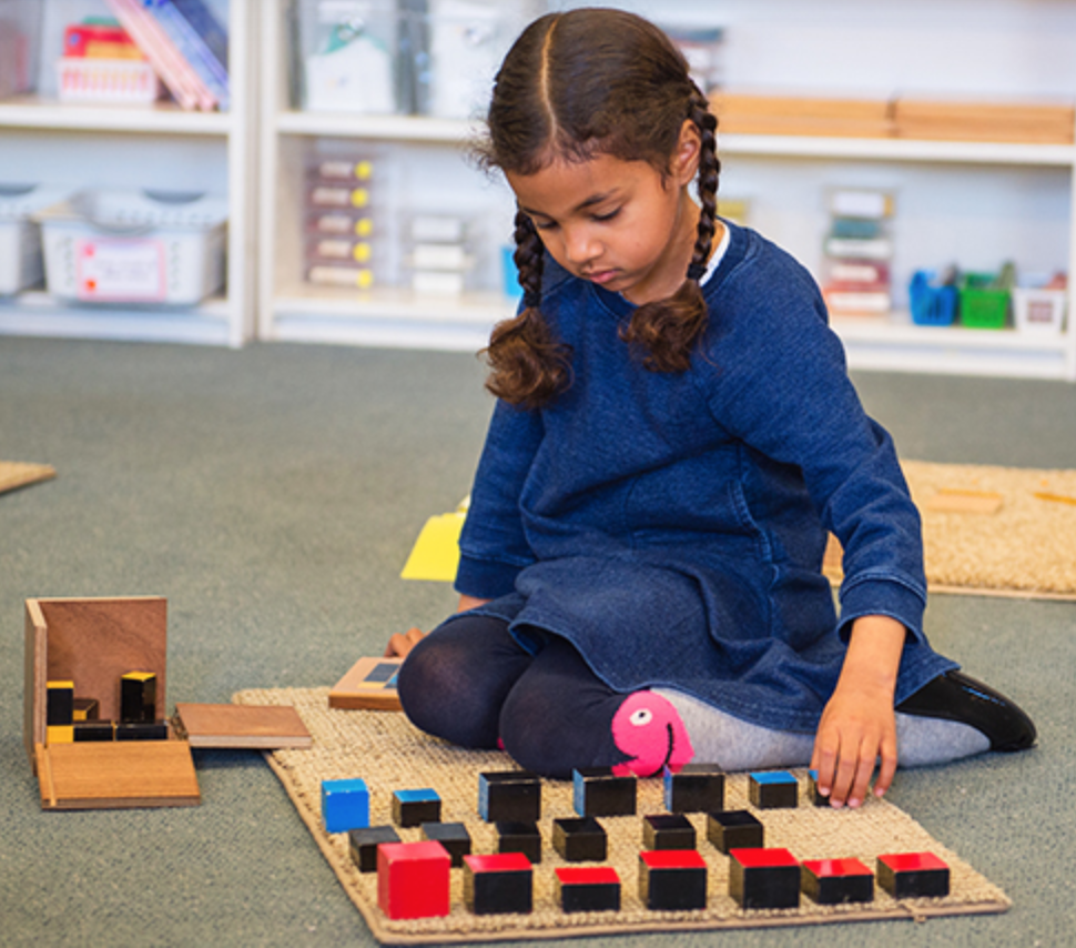 Child playing on the floor with Montessori toys